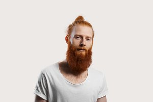 Kind attractive red beard hipster with open mouth isolated on neutral background. Student in white t-shirt look to the camera and talk. Concept for sale ecological product and promotion health life.