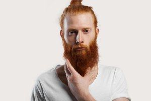 Close up portrait of red hair man with perfect skin with fleckles. Isolated portrait of attractive male with thinking emotion and hold his hot beard for relax. Kind hippie person with vegetarian view.