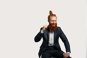 Happy and funny businessman laugh isolated on neutral background. Fashion red hair man in black suit friendly smiling with closed eyes. Glad person come into weekend for the party hard.