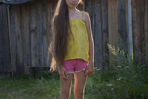 Teen girl with long hair in countryside yard, russian village