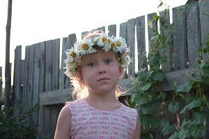 Cute little girl with flowers in hair - russian village
