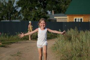 Little child girl joyful running on summer dusty rural road