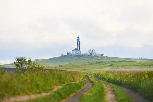 Road to lighthouse in grass. Romantic landscape near black sea in summer field. Perfect landscape with light clouds and sand way in green field.