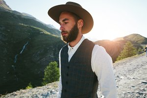 Hipster man walking in mountains