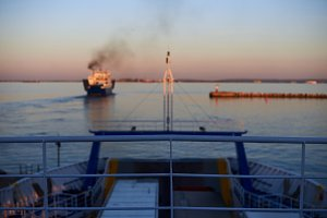 Cargo ship swimming in the evening sunset in blurred concept. Copy space for advertise services. View from top ferry desk.