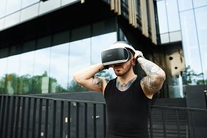 Strong and brutal man travel in city with virtual reality glasses. Sports guy testing VR system in streets of big city. Problem of internet playing.