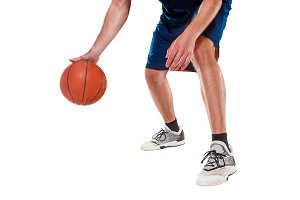 The legs of a basketball player with ball