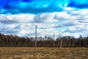 Power lines on spring field background
