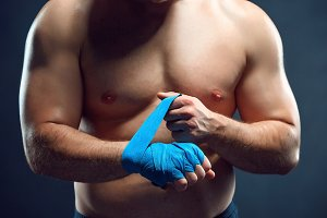 muscular boxer bandaging his hands on gray background