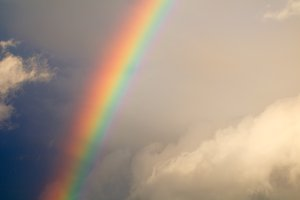 Beautiful rainbow after rain in the blue cloudy sky