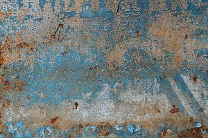 Background of peeling blue paint on an iron wall