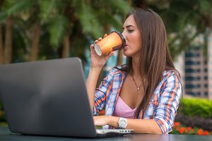 Young woman drinking coffee looking at the screen of her laptop in the park.