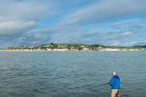 Male fisherman or angler off coast of Devon