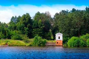 Vintage building on river bank landscape background