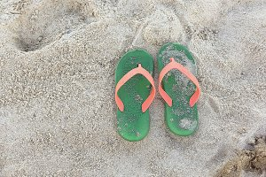 Green Orange Flipflops on a sandy