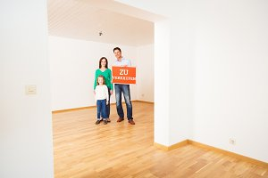 Family In Empty Apartment, Holding 'zu Verkaufen' Sign