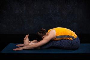 Woman practices Ashtanga Vinyasa yoga asana Paschimottanasana