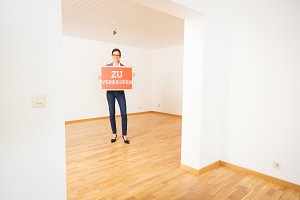 Realtor In Empty Apartment, Holding 'zu Verkaufen' Sign