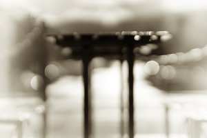 Sepia cafe table with benches bokeh background