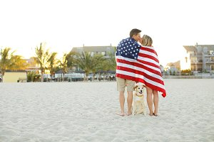 Couple wrapped in American Flag kiss