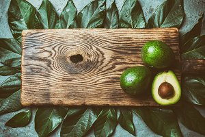 food background with fresh avocado, avocado tree leaves and wooden cutting board. Harvest concept, Guacamole ingredients. Healthy fat, omega 3. Half of avocado. Top view. Copy space.