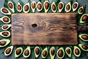Avocado. Frame made from avocado palta and avocado tree leaves around wooden board. Guacamole ingredients. Healthy fat, omega 3. Half of avocado. Top view. Copy space.