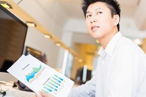 Young Asian Office Worker With Charts