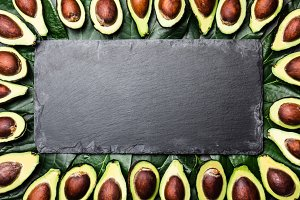 Avocado. Frame made from avocado palta and avocado tree leaves around slate board. Guacamole ingredients. Healthy fat, omega 3. Half of avocado. Top view. Copy space.