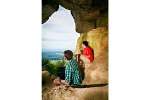 Young Couple Standing At Cave Entrance