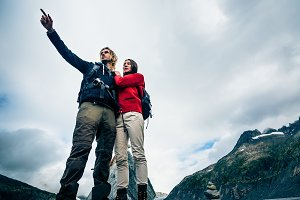 Young Couple Standing On The Mountain's Peak
