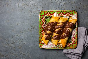 Mexican cuisine. Traditional Mexican chicken enchiladas with spicy chocolate salsa mole poblano. Enchiladas with sauce moole from Puebla, Mexico