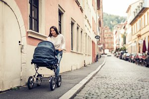 Young Mother With Baby Stroller In The City