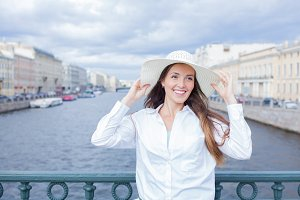 A beautiful and smiling girl in a white hat with wide brim is standing on the bridge and talking on the phone against the background of blue storm clouds