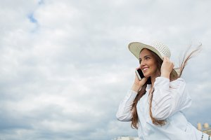 A beautiful and smiling girl in a white hat with wide brim is standing on the bridge and talking on the phone against the background of blue clouds
