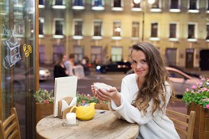 Young attractive girl sitting in the evening in a cafe with a Cup of tea to the backdrop of passing cars and city life. She looks at the camera and smiling
