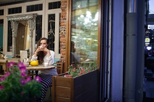 Young attractive girl sitting in the evening in the bright and warm cafe with a Cup of tea and looking out the window. The street is dark and cold. The concept of comfort