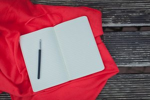 Blank Notepad with a black pen lying on a red blanket. Dark wooden background