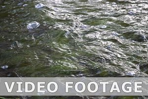 Water stream with waves and bubbles in slow motion