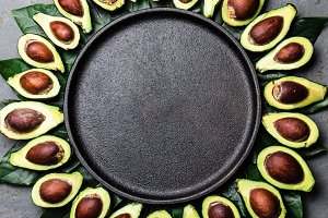 Avocado. Frame made from avocado palta and avocado tree leaves around black plate. Guacamole ingredients. Healthy fat, omega 3. Half of avocado. Top view. Copy space.