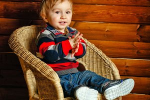 Boy sitting in wicker chair