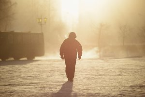 man walking in winter fog