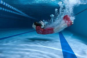 Swimmer in the dress dives underwater.