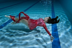 Woman's dress flutters under the water.