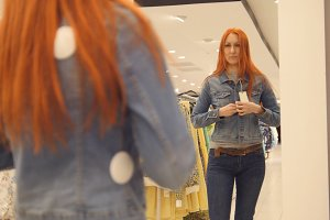 Girl chooses a jeans jacket, shopping for women