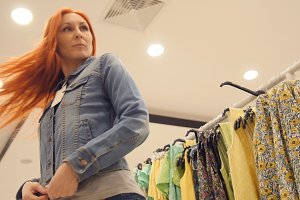 Young attractive woman is choosing a jeans jacket in women's clothing store