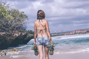 Sexy tropical woman walking on the beach with exotic pineapple fruit, paradise island of Bali. Healthy diet concept. Indonesia.