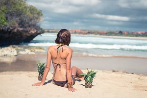 Sexy tropical woman sitting on the beach with exotic pineapple fruit, paradise island of Bali. Healthy diet concept. Indonesia.