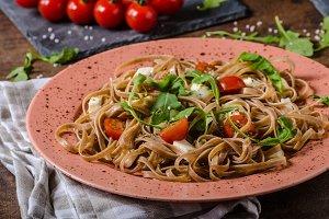 Spaghetti with mozzarella, cherry tomatoes and arugula