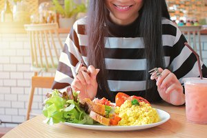 Young woman smiling and eating salad