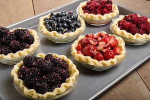 Fresh fruit pies on baking pan